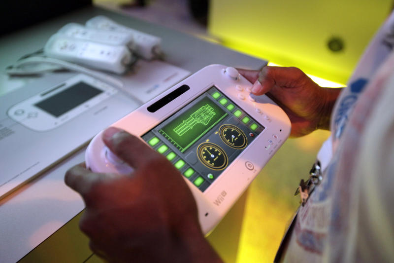 An attendee plays a video game using Nintendo's Wii U controller at E3 2012 in Los Angeles, Tuesday, June 5, 2012. Nintendo unleashed 23 games for its upcoming console featuring a touchscreen controller at the Electronic Entertainment Expo, or E3, the gaming industry's annual trade show. (AP Photo/Jae C. Hong)