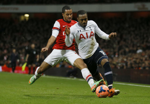 Arsenal's Theo Walcott, left challenges Tottenham's Danny Rose for the ball, Walcott was injured in the challenge during the English FA Cup third round soccer match between Arsenal and Tottenham Hotspur at the Emirates Stadium in London, Saturday, Jan. 4, 2014. (AP Photo/Kirsty Wigglesworth)