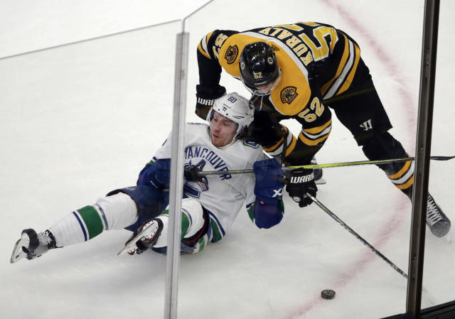 Vancouver Canucks center Markus Granlund (60) and Boston Bruins center Sean Kuraly (52) compete for the puck during the third period of an NHL hockey game Thursday, Nov. 8, 2018, in Boston. The Canucks won 8-5. (AP Photo/Elise Amendola)