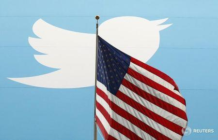 The Twitter Inc. logo is shown with the U.S. flag during the company's IPO on the floor of the New York Stock Exchange in New York