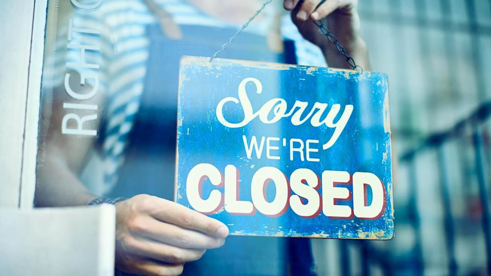 Midsection of barista hanging closed sign on window.