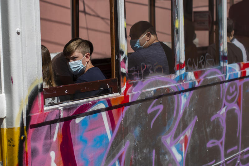 Passengers wear face masks for protection against the new coronavirus while riding on a tram in Lisbon, Portugal, Friday, Aug. 14, 2020. Portuguese health authorities have advised people to wear face masks when using public transport to help stem the spread of COVID-19. (AP Photo/Manu Fernandez)