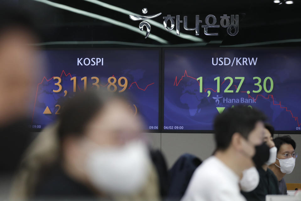 Currency traders watch computer monitors near screens showing the Korea Composite Stock Price Index (KOSPI), left, and the foreign exchange rate between U.S. dollar and South Korean won at the foreign exchange dealing room of the KEB Hana Bank headquarters in Seoul, South Korea, Friday, April 2, 2021. Asian shares were higher Friday after a broad rally pushed the S&P 500 past 4,000 points for the first time. (AP Photo/Lee Jin-man)