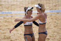 April Ross, left, of the United States, hugs teammate Alix Klineman after winning a women's beach volleyball match against Germany at the 2020 Summer Olympics, Tuesday, Aug. 3, 2021, in Tokyo, Japan. (AP Photo/Petros Giannakouris)