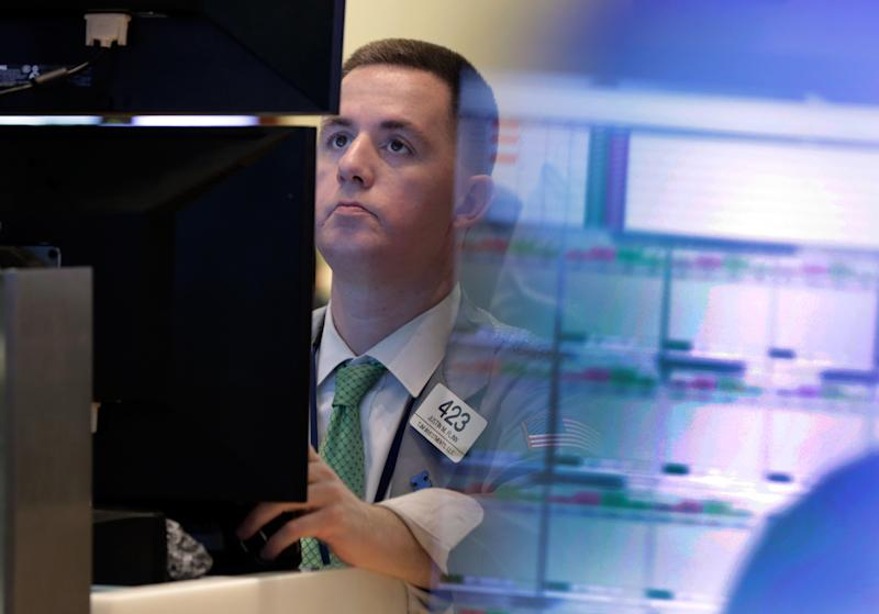 Trader Justin Flinn works in a booth on the floor of the New York Stock Exchange Monday, July 8, 2013. Stocks rose in early trading Monday ahead of the start of second-quarter corporate earnings reports. (AP Photo/Richard Drew)
