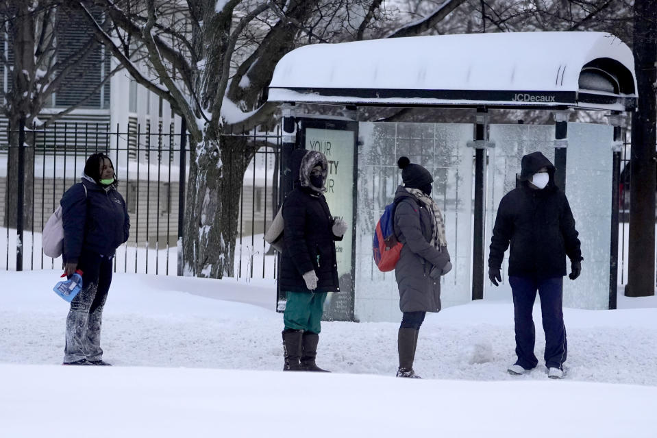 Commuters wait in the street Tuesday, Feb. 16, 2021, for a Chicago Transit Authority bus in the Bronzville neighborhood of Chicago. A winter storm has blanketed the Chicago area overnight with up to 18.5 inches of snow. (AP Photo/Charles Rex Arbogast)