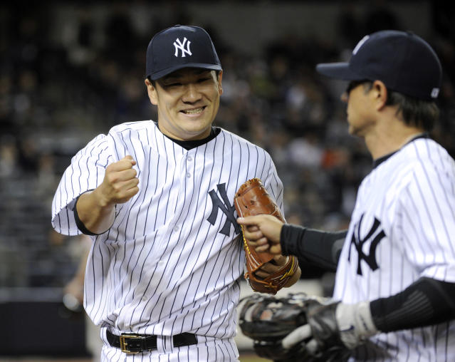 New York Yankees pitcher Masahiro Tanaka, left, reacts with second baseman Brian Roberts after Roberts made a play to get out Baltimore Orioles' Ryan Flaherty to end the sixth inning of a baseball game Wednesday, April 9, 2014, at Yankee Stadium in New York. (AP Photo/Bill Kostroun)