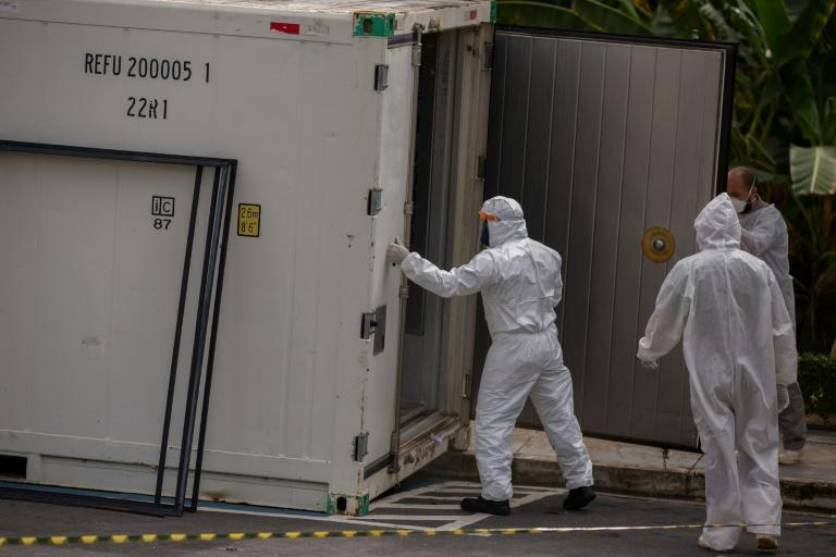 Health workers wear protective suits as they leave a body of a victim of the novel coronavirus in a refrigerated container at the Vinte Oito de Agosto Public Hospital, a unit treating COVID-19 patients in Manaus, Brazil January 4, 2021