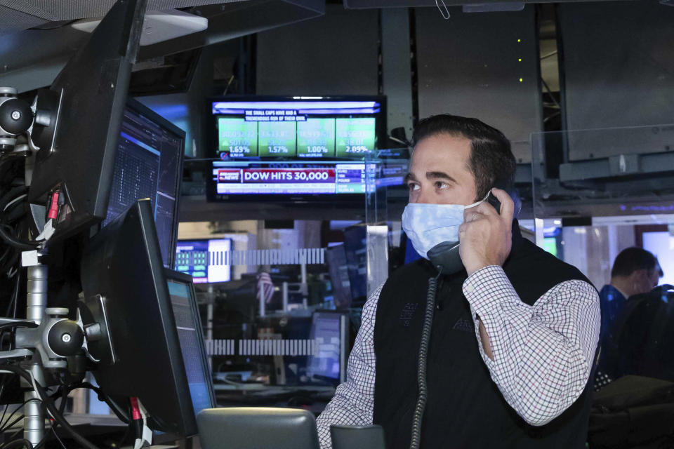 A trader at the New York Stock Exchange works at his terminal, Tuesday, November 24, 2020. The Dow Jones Industrial Average traded above 30,000 points for the first time as investors were encouraged by the latest progress on developing coronavirus vaccines and news that the transition of power in the U.S. to President-elect Joe Biden will finally begin. (Nicole Pereira/NYSE via AP)