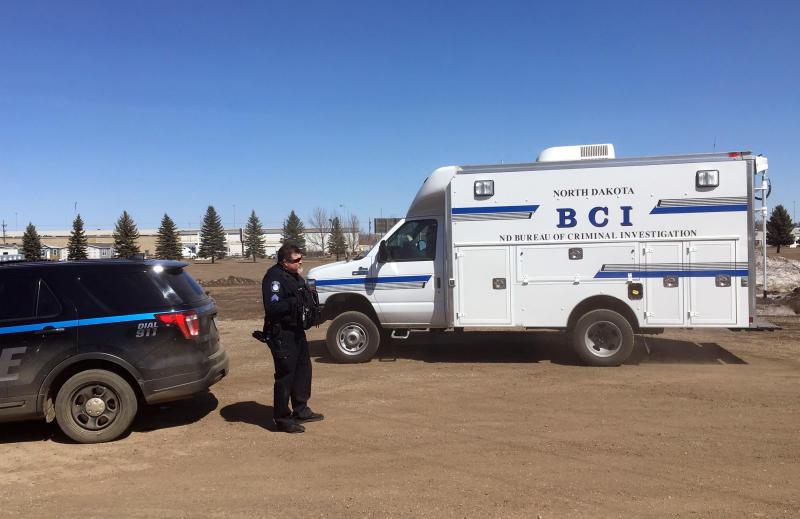 "In this Wednesday, April 3, 2019 photo, state and local police search a field in Manton, N.D., about half a mile from a business where an owner and three employees were found dead. Authorities on Thursday said they were looking for ""potential evidence"" related to the deaths discovered Monday at RJR Maintenance and Management in Mandan, a city just outside Bismarck. Police haven't yet identified a suspect. (AP Photo/ Blake Nicholson)"