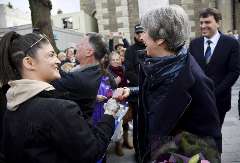Britain's Prime Minister Theresa May fist bumps a member of the public as she greets people after viewing the area where former Russian double agent Sergei Skripal and his daughter were found critically ill, in Salisbury, England, Thursday, March 15, 2018. May on Wednesday expelled 23 Russian diplomats, severed high-level contacts and vowed both open and covert action following the incident. (Toby Melville/Pool Photo via AP)