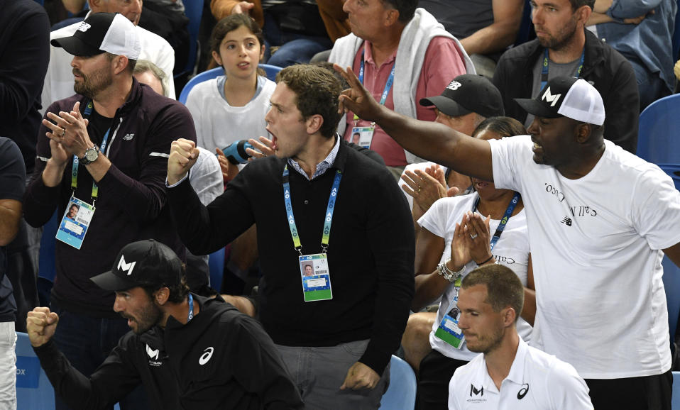 """Supporters of United States' Cori """"Coco"""" Gauff react as she won the first set tie-breaker against compatriot Venus Williams during their first round singles match at the Australian Open tennis championship in Melbourne, Australia, Monday, Jan. 20, 2020. (AP Photo/Andy Brownbill)"""