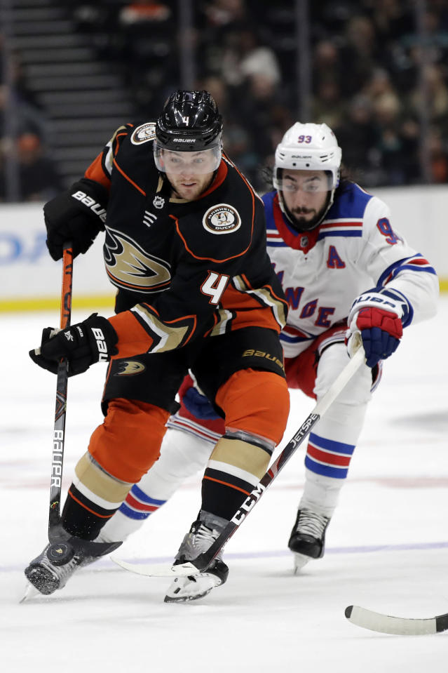 Anaheim Ducks' Cam Fowler, left, controls the puck in front of New York Rangers' Mika Zibanejad during the second period of an NHL hockey game Saturday, Dec. 14, 2019, in Anaheim, Calif. (AP Photo/Marcio Jose Sanchez)
