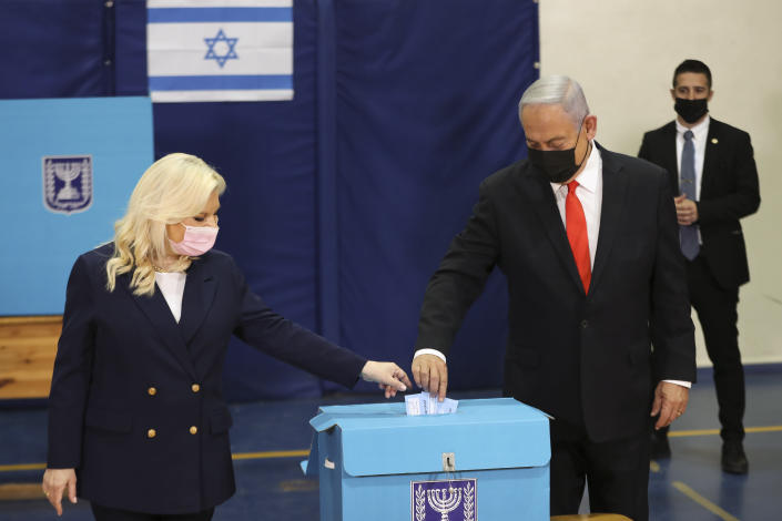 Israeli Prime Minister Benjamin Netanyahu and his wife Sara cast their ballots at a polling station as Israelis vote in a general election, in Jerusalem , Tuesday, March 23, 2021. Israelis began voting on Tuesday in the country's fourth parliamentary election in two years — a highly charged referendum on the divisive rule of Netanyahu. (Ronen Zvulun/Pool via AP)