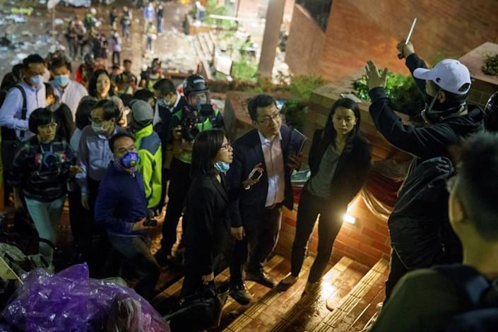 Teachers and relatives negotiate with protesters about the surrender of younger students from the occupied campus of the Hong Kong Polytechnic University that is surrounded by police in Hong Kong