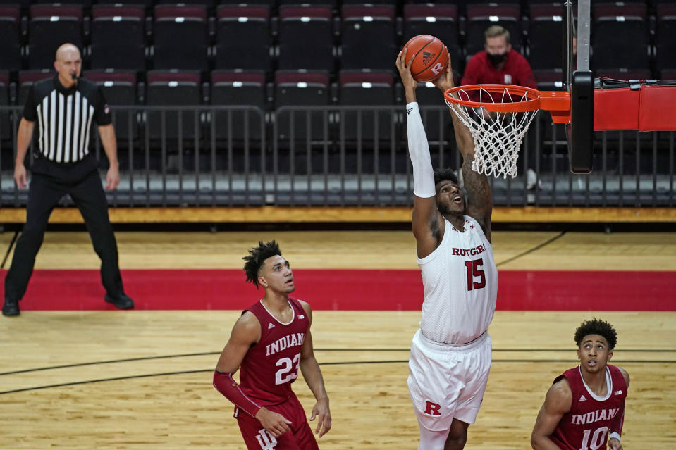 Rutgers center Myles Johnson (15) dunks between Indiana forward Trayce Jackson-Davis (23) and guard Rob Phinisee (10) during the second half of an NCAA college basketball game Wednesday, Feb. 24, 2021, in Piscataway, N.J. (AP Photo/Kathy Willens)