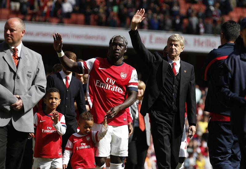 Arsenal's manager Arsene Wenger, center right, and Bacary Sagna, center left, wave to the supporters as the team parade around the stadium in their last home match of the season, after their English Premier League soccer match against West Bromwich Albion at Emirates Stadium in London, Sunday, May 4, 2014