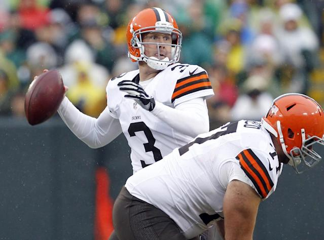 FILE - In this Oct. 20, 2013, file photo, Cleveland Browns' Brandon Weeden drops back during the first half of an NFL football game against the Green Bay Packers in Green Bay, Wis. The Dallas Cowboys added free agent Weeden on a two-year contract Monday, March 17, 2014. (AP Photo/Mike Roemer, File)