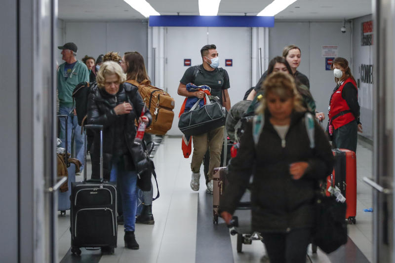 Travelers arrive at the international terminal of the O'Hare Airport in Chicago, Illinois, on March 15, 2020. - Chaos gripped major US airports Sunday as Americans returning from coronavirus-hit European countries overwhelmed authorities attempting to process the surge.Frustrated passengers complained of hours-long lines, crowded and unsanitary conditions and general disarray in the system for screening people for symptoms of the virus.Chaos gripped major US airports Sunday as Americans returning from coronavirus-hit European countries overwhelmed authorities attempting to process the surge. Frustrated passengers complained of hours-long lines, crowded and unsanitary conditions and general disarray in the system for screening people for symptoms of the virus. Schools, museums, sports arenas and entertainment venues have closed in some states, but St. Patrick's Day celebrations still filled bars and restaurants over the weekend, leading some local officials to consider more extensive shutdowns. (Photo by KAMIL KRZACZYNSKI / AFP) (Photo by KAMIL KRZACZYNSKI/AFP via Getty Images)