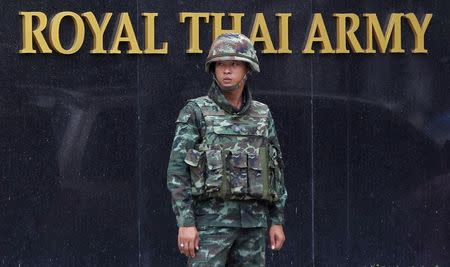 A Thai soldier stands guard outside the Royal Thai Army Headquarters as members of the Radio and Satellite Broadcasters gather in Bangkok