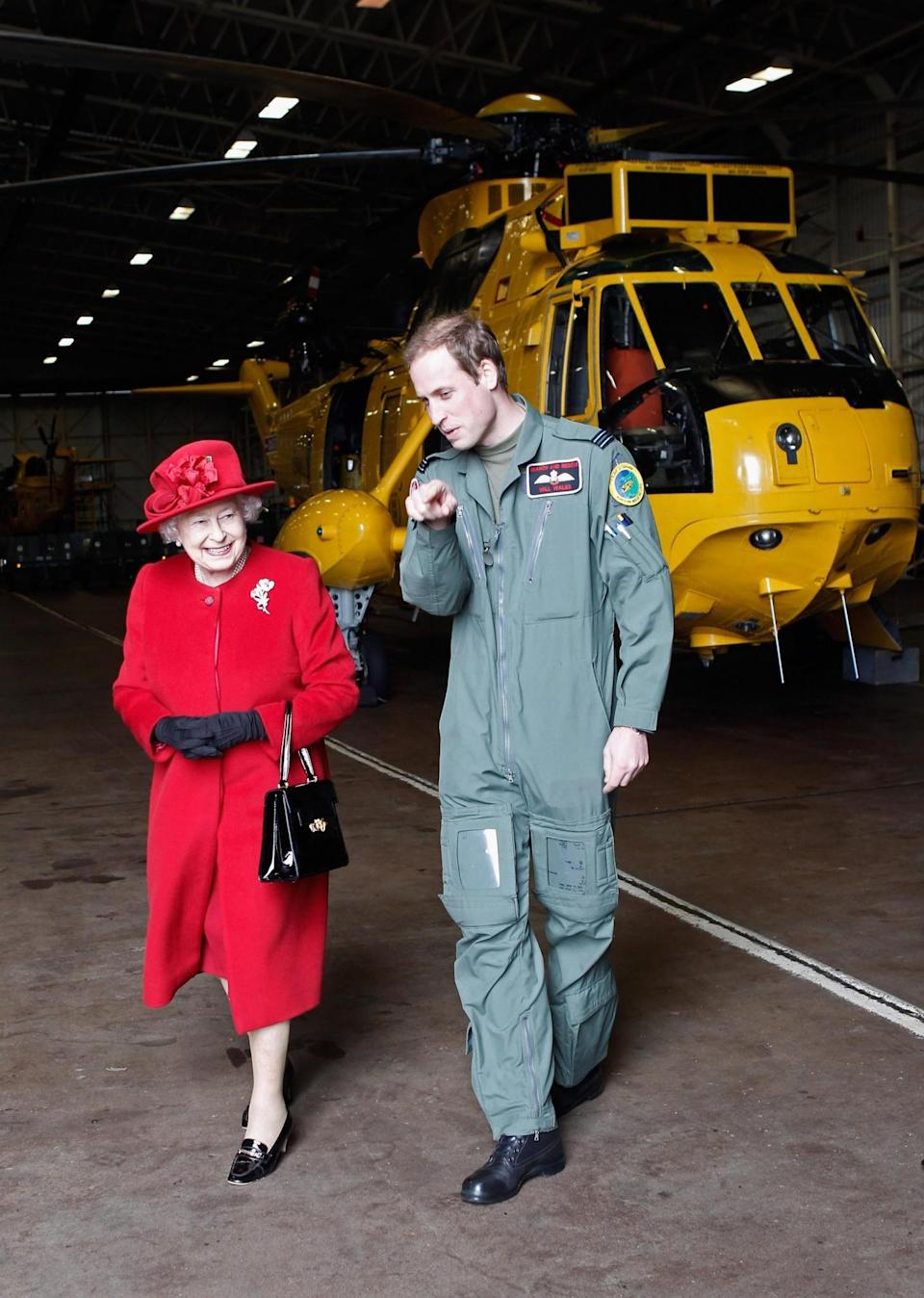 <p>Prince William shows Queen Elizabeth II the hanger where the helicopter he flies is kept in Anglesey. (PA) </p>