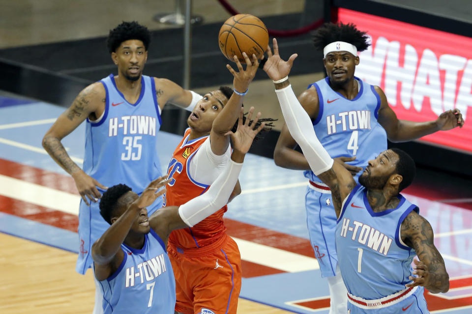 Oklahoma City Thunder center Moses Brown, middle, reaches for a rebound between, from left, Houston Rockets guard Victor Oladipo (7) center Christian Wood (35), forward Danuel House Jr. (4) and guard John Wall (1) during the second half of an NBA basketball game Sunday, March 21, 2021, in Houston. (AP Photo/Michael Wyke)