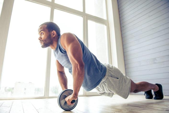 American sportsman is doing ab wheel rollout exercise and looking forward while working out at home