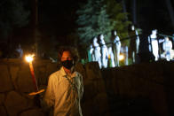 An Israeli scout holds a torch during a Memorial Day ceremony commemorating fallen soldiers, at the military cemetery at Mount Herzl in Jerusalem, Tuesday, April 13, 2021. (AP Photo/Maya Alleruzzo)