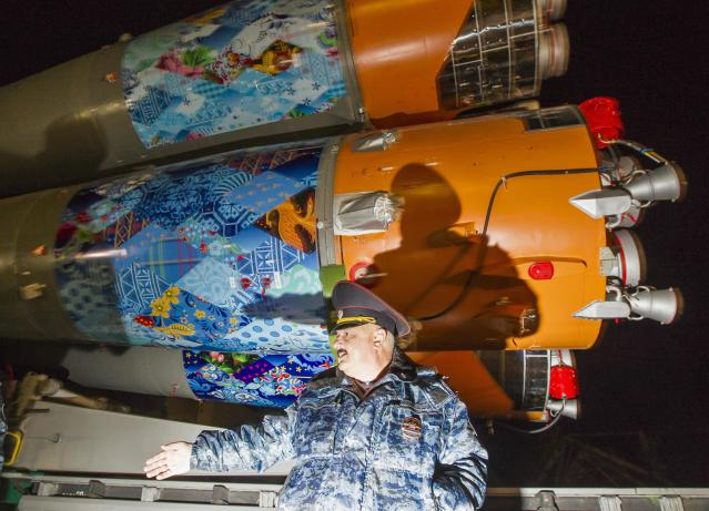 A police officer secures an area as the Soyuz TMA-11M spacecraft decorated with 2014 Sochi Winter Olympic Games' patterns, is transported to its launch pad at the Baikonur cosmodrome November 5, 2013. The Soyuz spacecraft will carry Japanese astronaut Koichi Wakata, Russian cosmonaut Mikhail Tyurin and U.S. astronaut Rick Mastracchio to the International Space Station (ISS) on November 7. REUTERS/Shamil Zhumatov (KAZAKHSTAN - Tags: SCIENCE TECHNOLOGY)