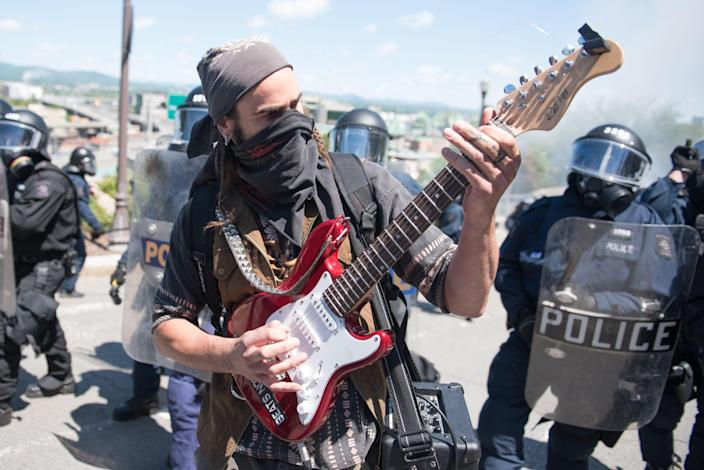 <p>Police look on as a protester plays guitar during a demonstration in Quebec City on June 8, 2018, as the G7 Summits gets underway. (Photo: Alice Chiche/AFP/Getty Images) </p>
