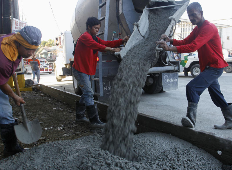 File Photo: Workers pour cement during roadworks, which are a part of the government's road rehabilitation projects, in Mandaluyong City Metro Manila November 28, 2012. REUTERS/Cheryl Ravelo
