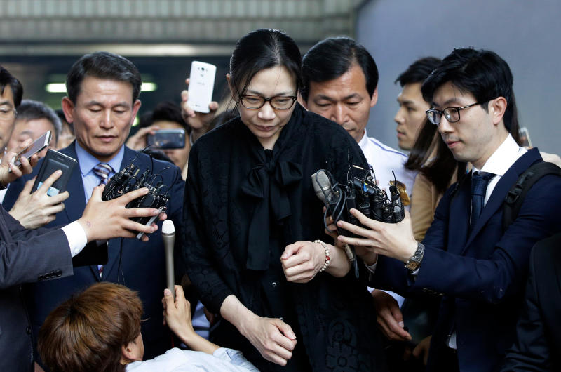FILE - In this May 22, 2015 file photo, former Korean Air executive Cho Hyun-ah, center, is surrounded by reporters as she leaves the Seoul High Court in Seoul, South Korea. Korean Air Lines said Monday, April 23, 2018, that two daughters of its chairman will resign from their executive positions amid mounting public criticism over the women's behavior and the family's smuggling allegations. (AP Photo/Lee Jin-man, File)