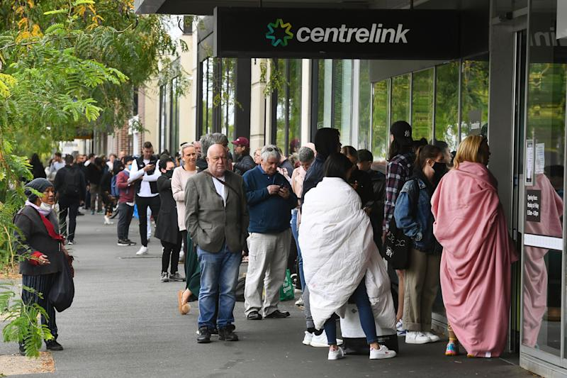 Hundreds of people queue outside an Australian government welfare centre, Centrelink, in Melbourne on March 23, 2020, as jobless Australians flooded unemployment offices around the country after Prime Minister Scott Morrison warned the coronavirus pandemic would cause an economic crisis akin to the Great Depression. - In scenes not seen in Australia for decades, queues stretched around the block at unemployment offices around the country as the forced closure of pubs, casinos, churches and gyms began at midday on March 23. (Photo by William WEST / AFP) (Photo by WILLIAM WEST/AFP via Getty Images)