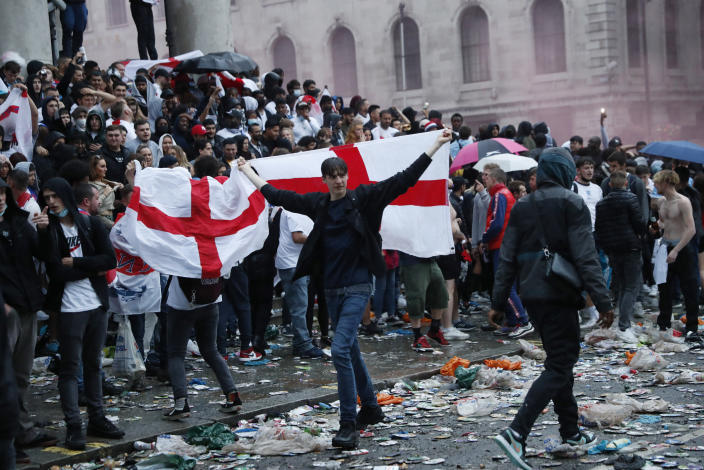 An England supporter waves a flag near Trafalgar Square in London, Sunday, July 11, 2021, during the Euro 2020 soccer championship final match between England and Italy which is being played at Wembley Stadium. (AP Photo/Peter Morrison)