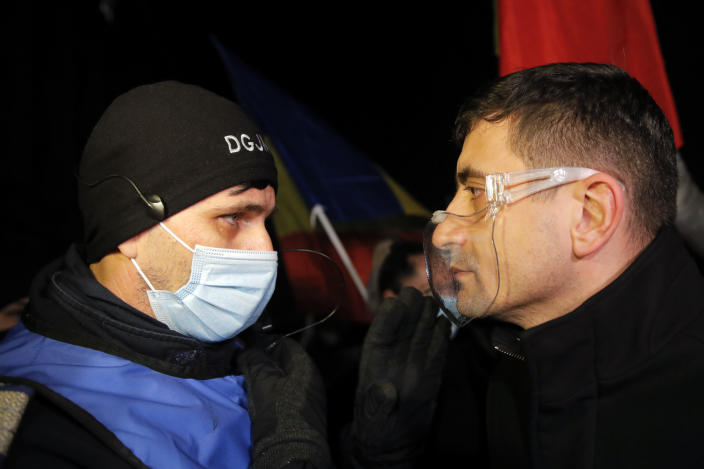 George Simion, one of the leaders of the Alliance for the Unity of Romanians or AUR, speaks to a gendarme during a protest outside the health ministry after a deadly fire at a hospital treating COVID-19 patients in Bucharest, Romania, Saturday, Jan. 30, 2021. Hundreds marched during a protest organized by the AUR alliance demanding the resignation of several top officials, after a fire early Friday at a key hospital in Bucharest that also treats COVID-19 patients killed five people. (AP Photo/Vadim Ghirda)