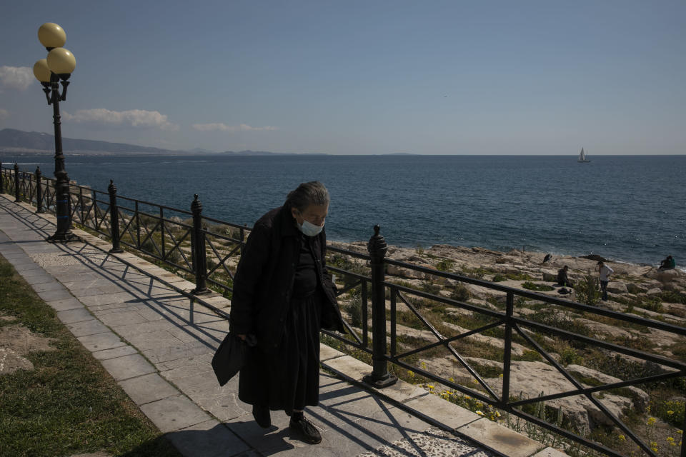 A woman wearing a face mask to prevent the spread of Covid-19 walks alongside a coast at Piraeus port town near Athens, Saturday, March 27, 2021. According to Greek authorities more than 1.5 million doses of the vaccine have been administered so far in the country, with nearly 1 million people receiving at least one jab. (AP Photo/Yorgos Karahalis)