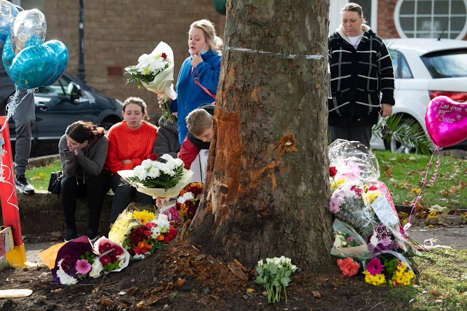 A photo of mourners at the scene of a fatal crash on Bromley Lane in Kingswinford, near Dudley.