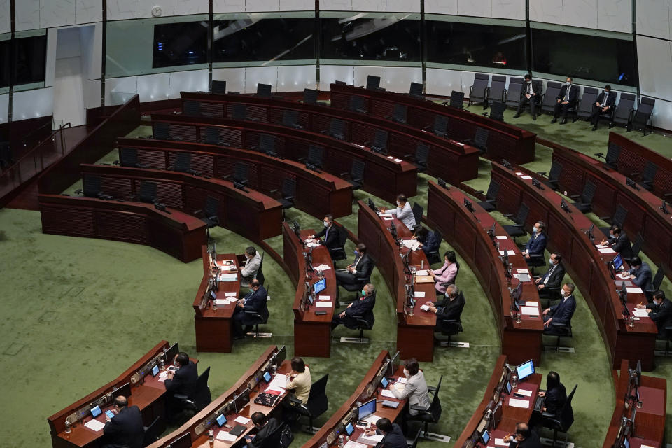 FILE - In this Nov. 25, 2020, file photo, empty seats of pro-democracy legislators, top, are seen as Hong Kong Chief Executive Carrie Lam delivers her policies at chamber of the Legislative Council in Hong Kong. A senior Chinese official says the largely pro-Beijing committee that currently elects the Hong Kong's leader will also elect some members of the city's legislature, as part of Beijing's planned revamp of Hong Kong's electoral system. (AP Photo/Kin Cheung, File)