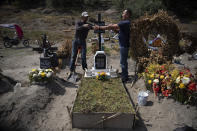 """Cemetery worker Jorge Arvizu, left, helps a family member place a plaque on the grave of Vicente Dominguez who died of complications related to the new coronavirus, at the municipal cemetery Valle de Chalco, on the outskirts of Mexico City, Tuesday, Oct. 20, 2020. Mexican families traditionally flock to local cemeteries to honor their dead relatives as part of the """"Dia de los Muertos,"""" or Day of the Dead celebrations, but according to authorities the cemeteries will be closed this year to help curb the spread of COVID-19. (AP Photo/Marco Ugarte)"""