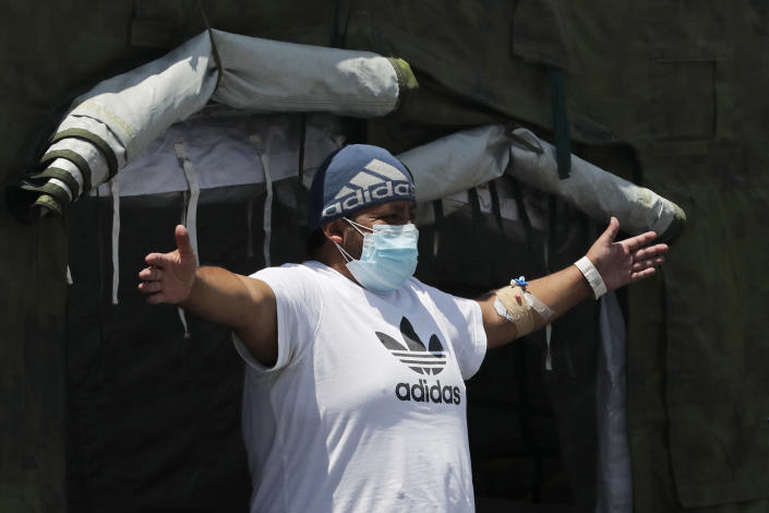 A COVID-19 patient does breathing exercises at the entrance of a tent set up to treat new coronavirus cases outside the Social Security Hospital, shortly before being released in Quito, Ecuador, Thursday, April 22, 2021. The government decreed new lockdown rules on April 21 for the majority of Ecuador's provinces, limiting movement on weeknights and an all-day curfew on weekends to curb the spread of the new coronavirus which is overwhelming hospitals. (AP Photo/Dolores Ochoa)
