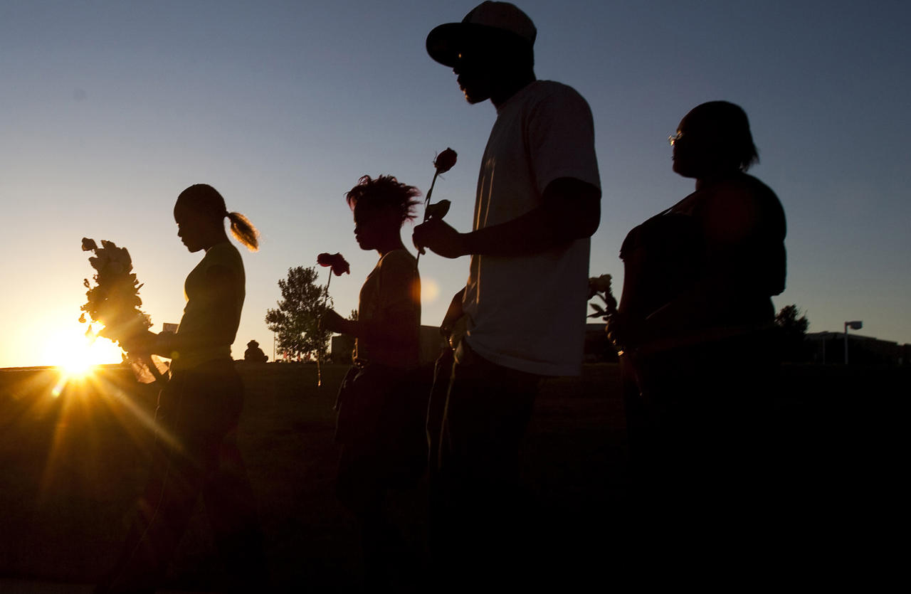 "From left, Tylecia Amos, 14, Shatyra Amos, 15, Michael Walker, 17, and Mykia Walker, 16, carry flowers to lay at a makeshift memorial across the street from the Century Theater parking lot, on Saturday, July 21, 2012 in Aurora, Colo. Twelve people were killed and dozens were injured in the attack early Friday at the packed theater during a showing of the Batman movie, ""Dark Knight Rises."" Police have identified the suspected shooter as James Holmes, 24. (AP Photo/Barry Gutierrez)"