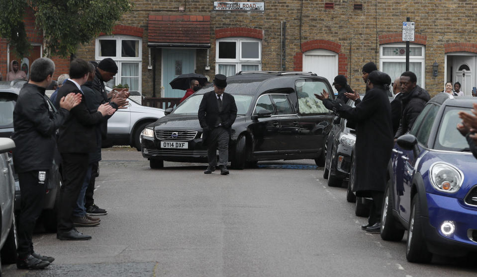 Grass roots soccer referees form a guard of honour and clap for the hearse with Jermaine Wright, a referee of the Hackney Marshes grassroots football league who died of COVID-19 in London, Thursday, June 11, 2020. (AP Photo/Frank Augstein)