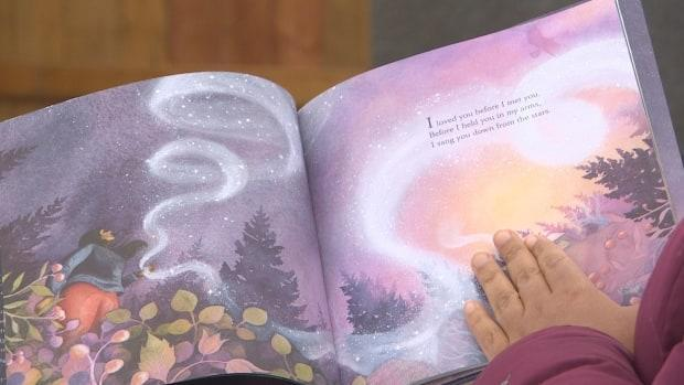 Spillett-Sumner reads over the first page of her book I Sang You Down From the Stars.