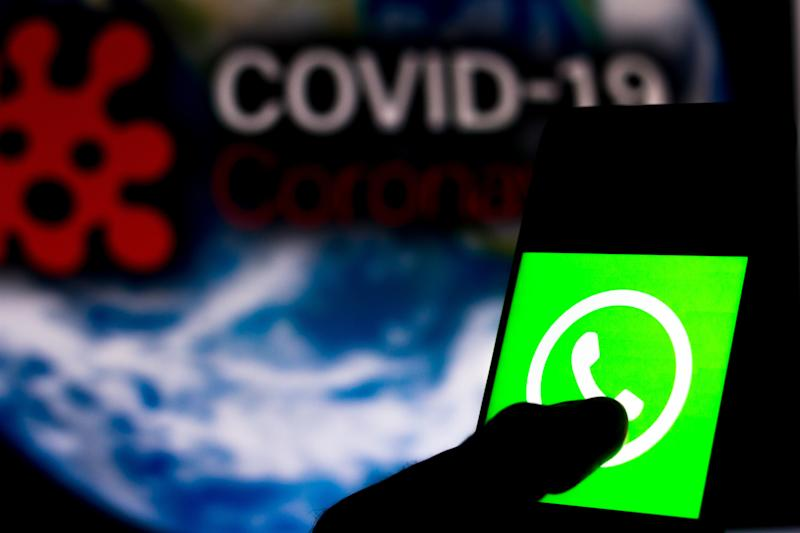 BRAZIL - 2020/04/05: In this photo illustration the WhatsApp logo seen displayed on a smartphone with a computer model of the COVID-19 coronavirus in the background. (Photo Illustration by Rafael Henrique/SOPA Images/LightRocket via Getty Images)