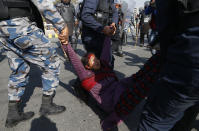 A pro-king supporter injured during clash with riot police is carried away as they march demanding reinstating monarchy that was abolished more than a decade ago in Kathmandu, Nepal, Monday, Jan.11, 2021. Monday's protest was the latest anti-government protest against Prime Minister Khadga Prasad Oli who has been facing street demonstrations against him from a splinter faction of his own Communist party and more from opposition political groups for dissolving parliament. Nepal's centuries-old monarchy was abolished in 2008 by the parliament and replaced by a republic where the president was elected as the head of state. (AP Photo/Niranjan Shrestha)