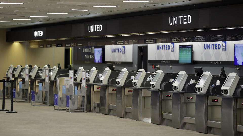 Empty United Airlines ticket machines are shown at the Tampa International Airport Friday, April 24, 2020, in Tampa, Fla. Business at the airport has been at a near standstill due to the coronavirus outbreak. (AP Photo/Chris O'Meara)