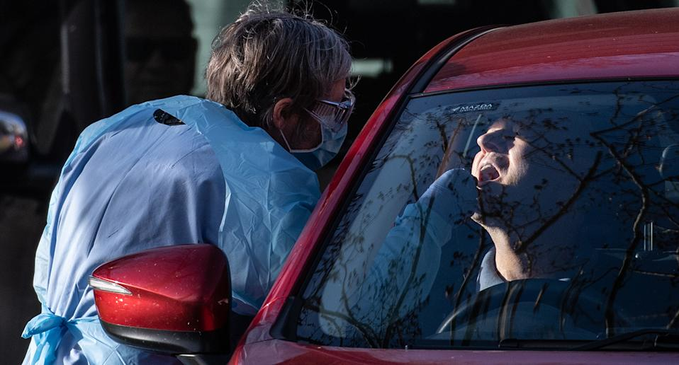 Healthcare workers conduct COVID-19 tests at a drive-through testing centre in Rozelle, Sydney, Friday, July 3, 2020. Health authorities are urging people in an inner-west Sydney suburb to be alert for COVID-19 symptoms after a local Woolworths worker tested positive for the virus. (AAP Image/James Gourley) NO ARCHIVING
