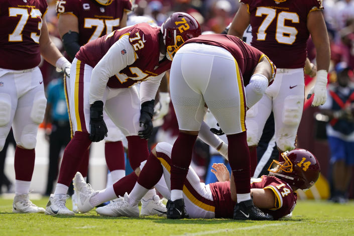 Members of the Washington Football Team check on condition of teammate quarterback Ryan Fitzpatrick (14) who lays on the field after being injured on a hit by Los Angeles Chargers linebacker Uchenna Nwosu during the first half of an NFL football game, Sunday, Sept. 12, 2021, in Landover, Md. (AP Photo/Alex Brandon)