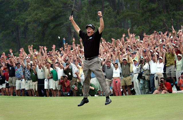 FILE - In this April 11, 2004, file photo, taken by Dave Martin, Phil Mickelson celebrates after winning the Masters golf tournament with at the Augusta National Golf Club in Augusta, Ga. Martin, a longtime Associated Press photographer based in Montgomery, Ala., died after collapsing on the Georgia Dome field at the Chick-fil-A Bowl on Tuesday, Dec. 31, 2013. Martin was 59.(AP Photo/Dave Martin, File)