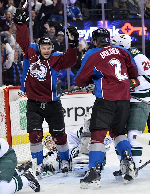 Colorado Avalanche left wing Jamie McGinn, left, and Nick Holden (2) celebrate Holden's power play goal against Minnesota Wild goalie Darcy Kuemper in the first period during Game 7 of an NHL hockey first-round playoff series on Wednesday, April 30, 2014, in Denver. (AP Photo/Jack Dempsey)